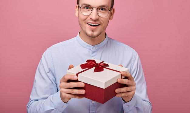 L'uomo piacevolmente sorpreso tiene il regalo in scatola con il coperchio rosso