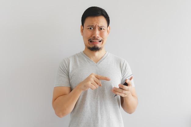 L'uomo piange e triste con quello spettacolo sullo smartphone.