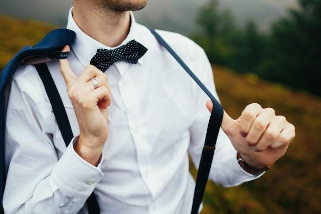 L'uomo pone in camicia bianca con bretelle