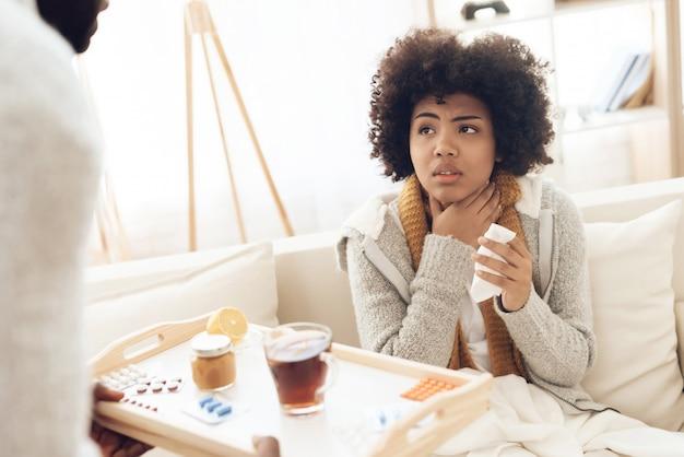 L'uomo porta il tè e la medicina per la donna malata seduta sul divano.