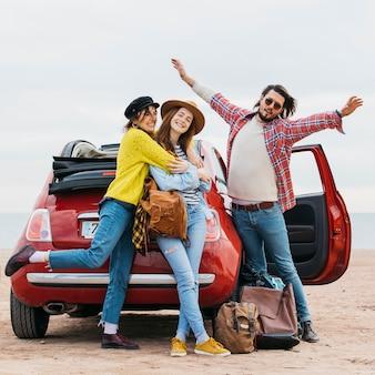 L'uomo positivo con le mani alzate si avvicina ad abbracciare le donne e l'automobile sulla spiaggia
