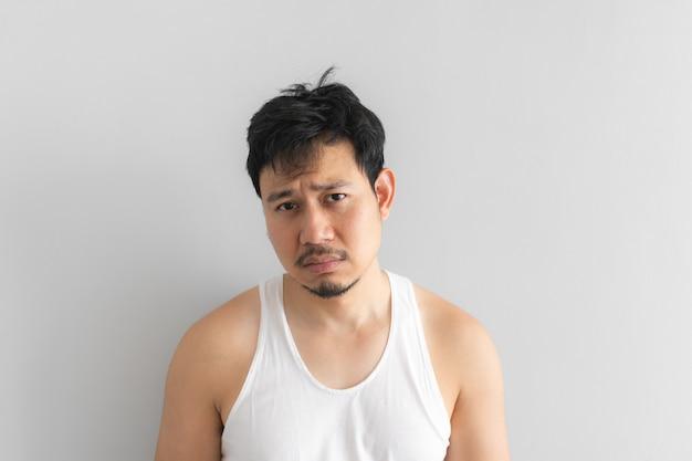 L'uomo povero e depresso indossa canotta bianca su sfondo grigio. concetto di vita disperata.