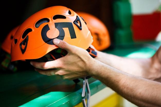 L'uomo prende un casco arancione con un numero cinque