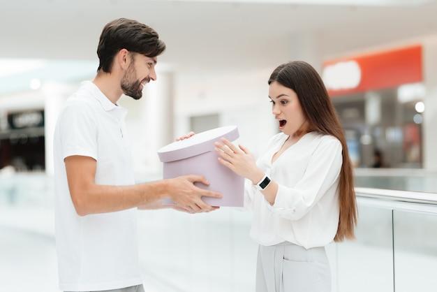 L'uomo presenta la donna con la nuova scatola rotonda con l'acquisto.
