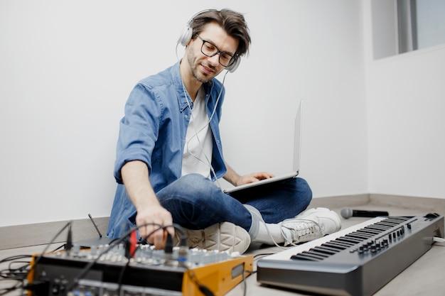 L'uomo produce la colonna sonora elettronica o la traccia nel progetto a casa