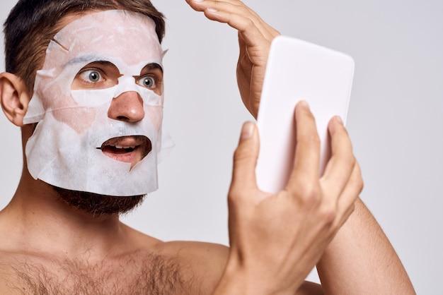 L'uomo produce maschere in tessuto cosmetico, cura della pelle del viso a casa