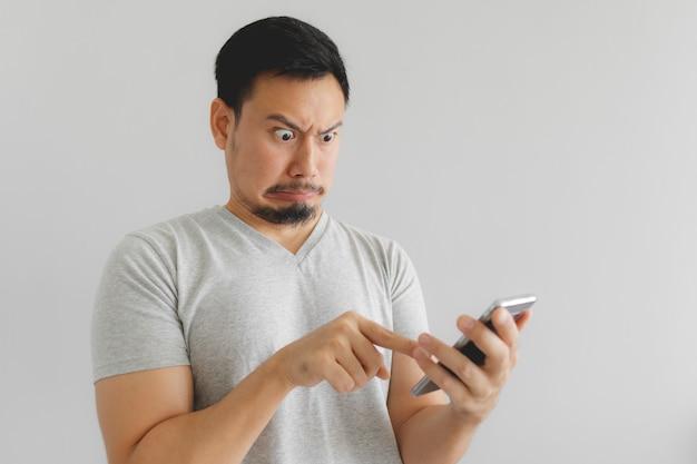 L'uomo prova odio e disgusto per ciò che mostra sullo smartphone.