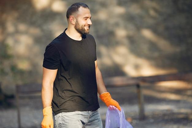 L'uomo raccoglie l'immondizia nei sacchetti di immondizia in parco