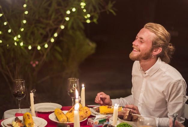 L'uomo ridendo mentre era seduto al tavolo festivo