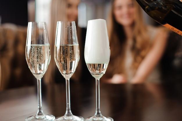 L'uomo riempie bicchieri di champagne per tre belle giovani donne