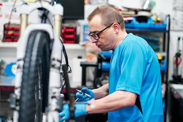 L'uomo ripara una bici nella sua piccola officina