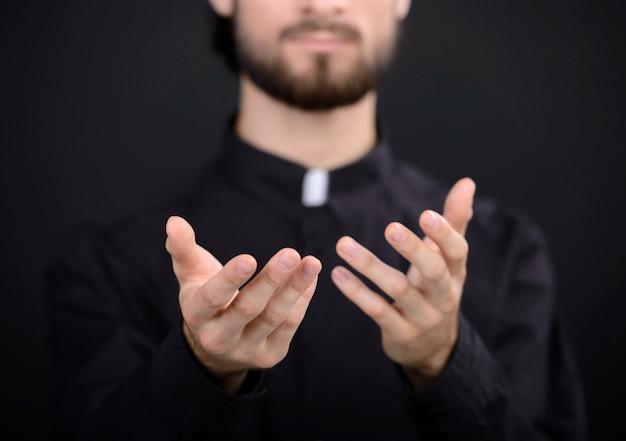 L'uomo sacerdote gli tiene le mani davanti e prega.