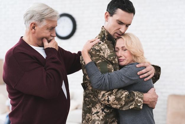 L'uomo saluta la sua famiglia e i suoi genitori.