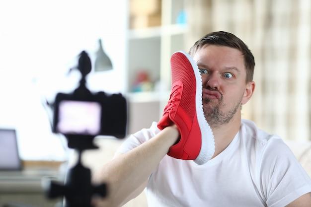 L'uomo scatta foto con la faccia di sneaker, fotocamera frontale
