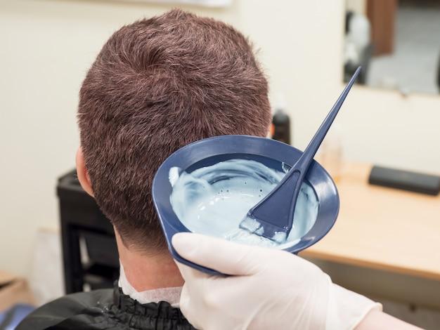 L'uomo sceglie la vernice per tingere i capelli. l'uomo tonifica i suoi capelli.