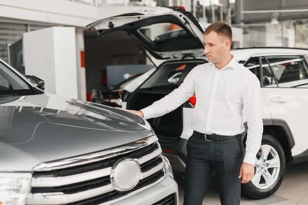 L'uomo sceglie un'auto in concessionaria, tocca l'automobile grigia della business class.