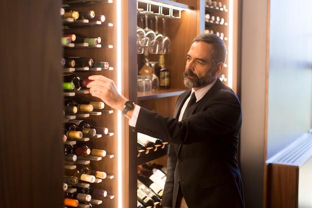 L'uomo sceglie una bottiglia di vino