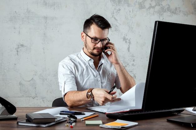 L'uomo seduto a un tavolo in ufficio, parlando al telefono, decide una domanda importante. il concetto di lavoro d'ufficio, una startup. copia spazio.