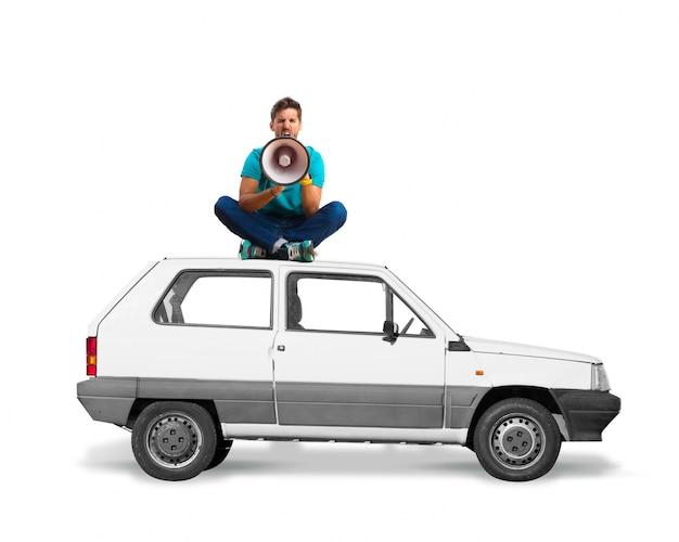 L'uomo seduto sul tetto di una macchina con un megafono grida