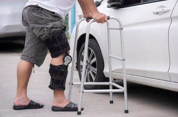 L'uomo senior apre la portiera della macchina con un camminatore sulla strada
