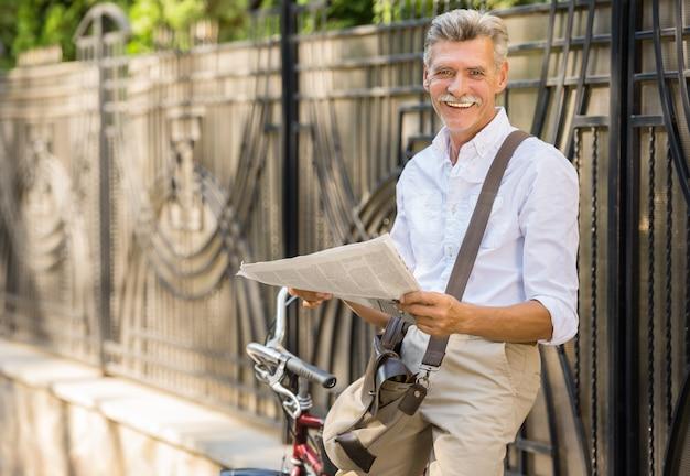 L'uomo senior sta leggendo il giornale mentre si sedeva sulla bicicletta.