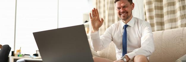 L'uomo senza pantaloni si siede davanti al computer portatile a casa