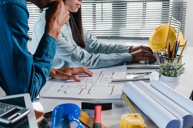 L'uomo serio dell'ingegnere dell'architetto e la progettazione del womna seri che lavorano e che discutono i dati e lap