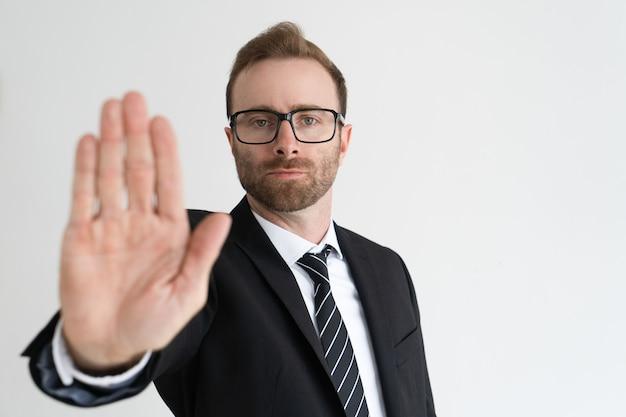 L'uomo serio di affari che mostra la palma aperta o ferma il gesto e l'esame della macchina fotografica.