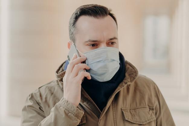 L'uomo serio parla al telefono, indossa una maschera medica per proteggersi dai virus nei luoghi pubblici. il paziente infetto ha covid-19.