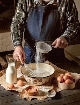 L'uomo setaccia la farina e impasta la pasta