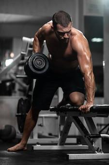 L'uomo si allena in palestra. l'uomo atletico si allena con i manubri, pompando i suoi bicipiti