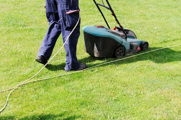 L'uomo si muove con la falciatrice e falcia l'erba verde