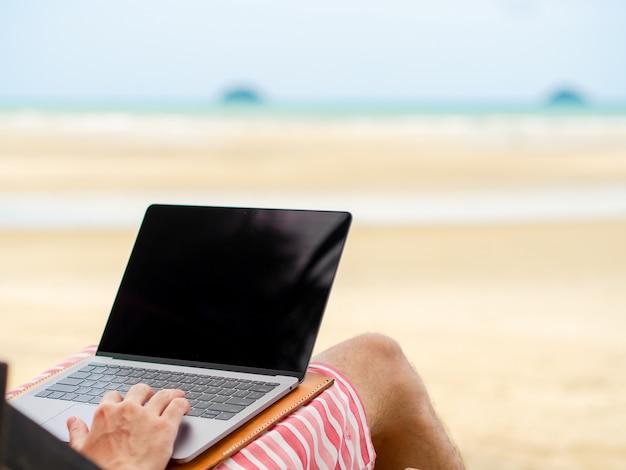 L'uomo si rilassa sul letto da campo e lavora online.
