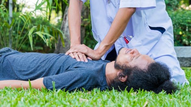 L'uomo si sdraiò sull'erba e il dottore con la camicia bianca a maniche lunghe aiuta la rcp