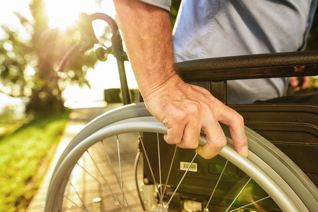 L'uomo si siede in sedia a rotelle. assistenza per disabili.