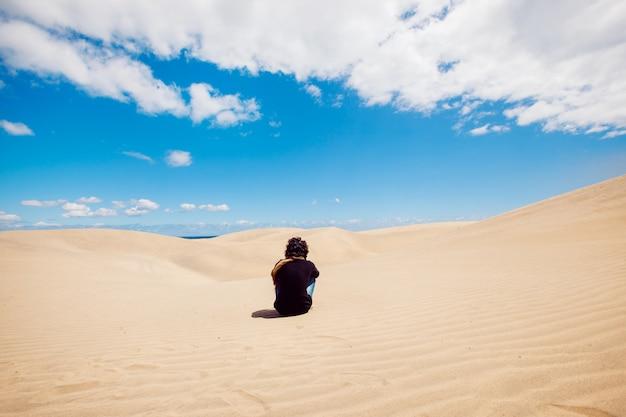 L'uomo si siede su un paesaggio di dune del deserto. uomo che fa un giro turistico tra le dune in una calda giornata estiva.