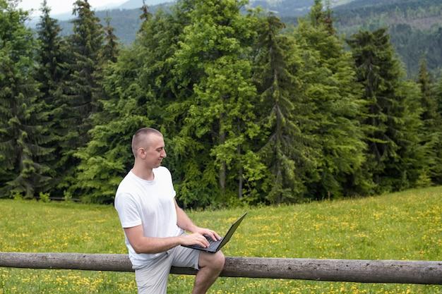 L'uomo si siede su una staccionata di legno e lavora con un computer portatile vicino al campo e alla foresta di conifere
