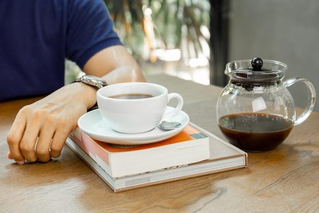 L'uomo si siede sul tavolo con caffè sul libro in caffetteria.