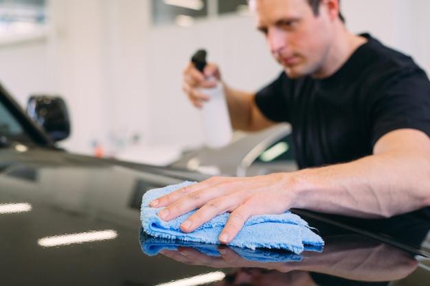 L'uomo si sta asciugando con un corpo di stoffa di una macchina brillante.