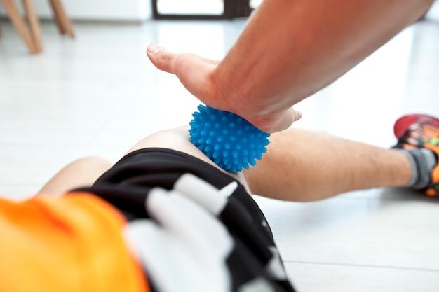 L'uomo si sta massaggiando la gamba massaggiando la palla a casa