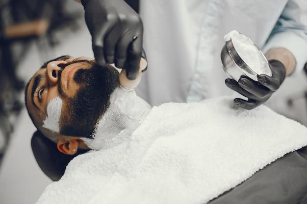 L'uomo si taglia la barba nel barbiere.