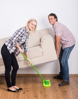 L'uomo solleva il divano mentre la ragazza pulisce.