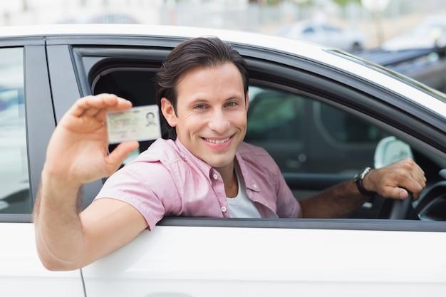 L'uomo sorride e tiene la sua patente di guida