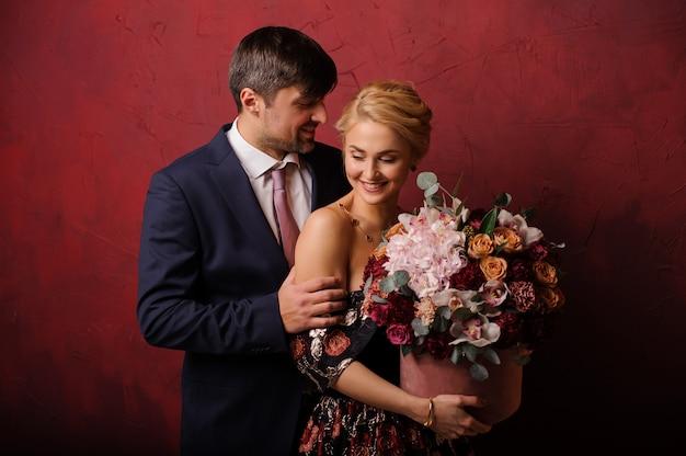 L'uomo sorridente abbraccia la sua donna con il mazzo di fiori