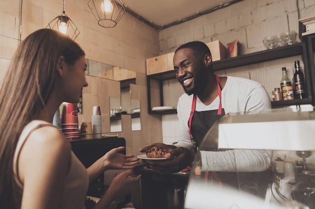 L'uomo sorridente del barista dà ad una ragazza il suo ordine