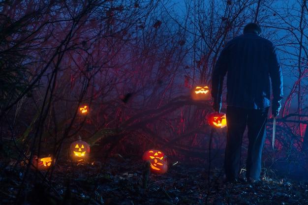 L'uomo spaventoso nella foresta di notte sta tagliando le zucche di halloween