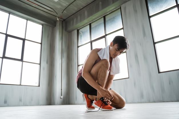 L'uomo sport allaccia le scarpe prima dell'allenamento