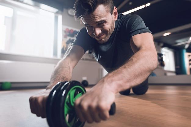L'uomo sportivo sta facendo gli esercizi con la ruota della palestra.