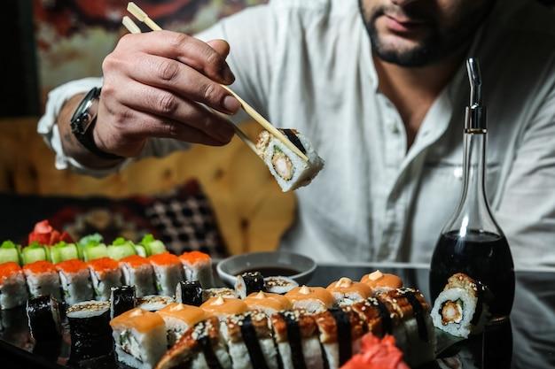 L'uomo sta andando a mangiare la vista laterale della salsa di soia del wasabi dello zenzero dei sushi