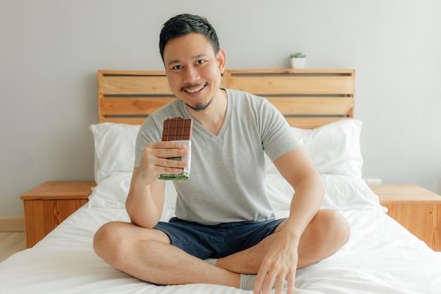L'uomo sta bevendo una tazza di caffè sul letto nella sua camera da letto.